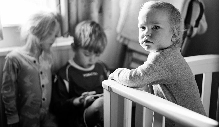 Toddler looking at camera from his cot