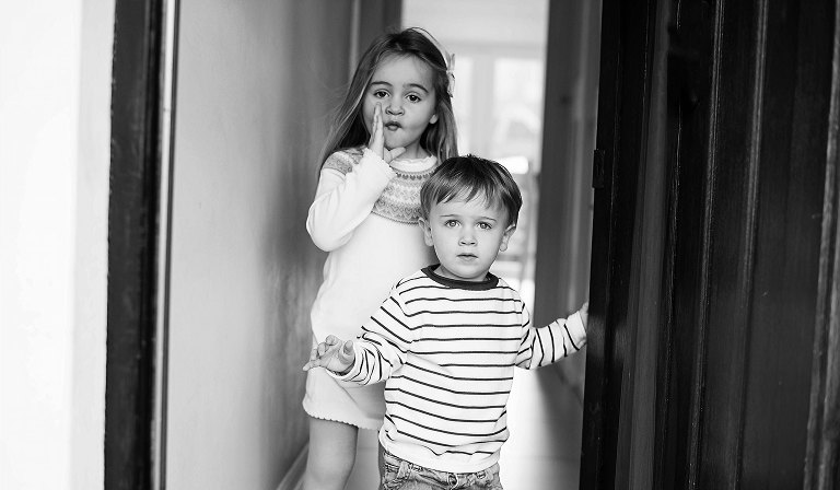 Siblings stand by the front door