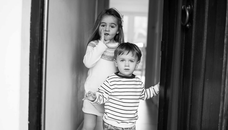 Brother and sister standing by door